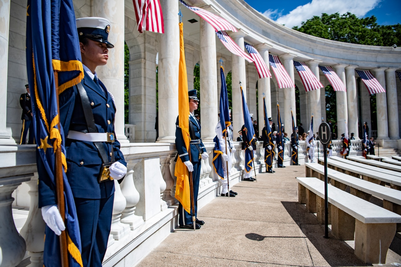 Service members stand at attention in an amphitheater.