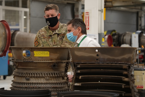 Two men with an aircraft engine part in front of them.