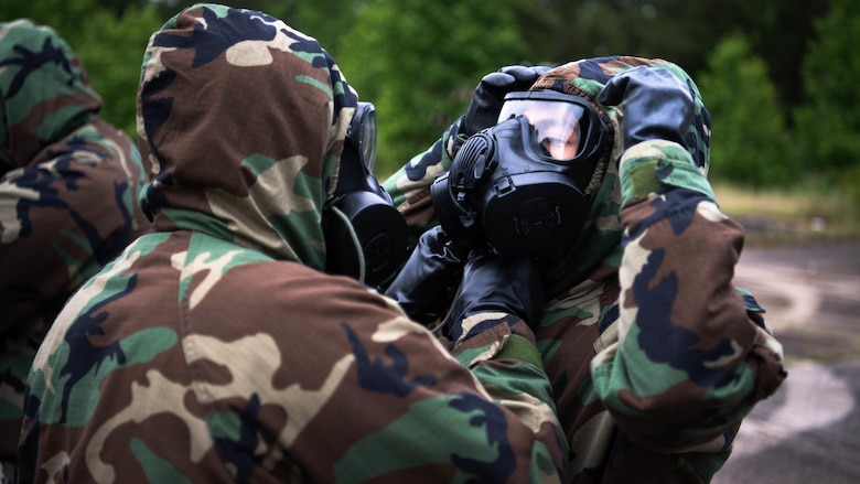 """Airmen from the 2nd Civil Engineer Squadron perform """"buddy checks'' after donning mission oriented protective posture gear during a 2nd CES training exercise at Barksdale Air Force Base, Louisiana, May 20, 2021. The exercise showcased contingency skills such as: land navigation, self-aid buddy care and chemical, biological, radiological and nuclear preparedness. (U.S. Air Force photo by Senior Airman Jacob B. Wrightsman)"""