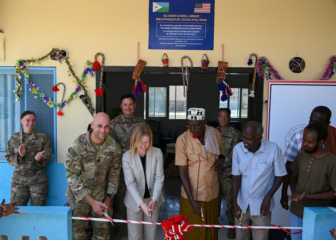 U.S. Army Reserve Capt. Sultan Durzi, left, team chief of Civil Affairs East Africa Southern European Task Force Africa, in support of Combined Joint Task Force-Horn of Africa, Liz Canellakis, center left, public diplomacy officer for the U.S. Embassy, Hassan Samreh, right center, chief of Ali Adde village, and Mahamoud Robleh, right, director of Ali Adde School, cut the ribbon during the inauguration ceremony of the new Ali Adde school library in Ali Adde, Djibouti, May 27, 2021. The library marks the third U.S.-funded library completed within Djibouti with more in the works.