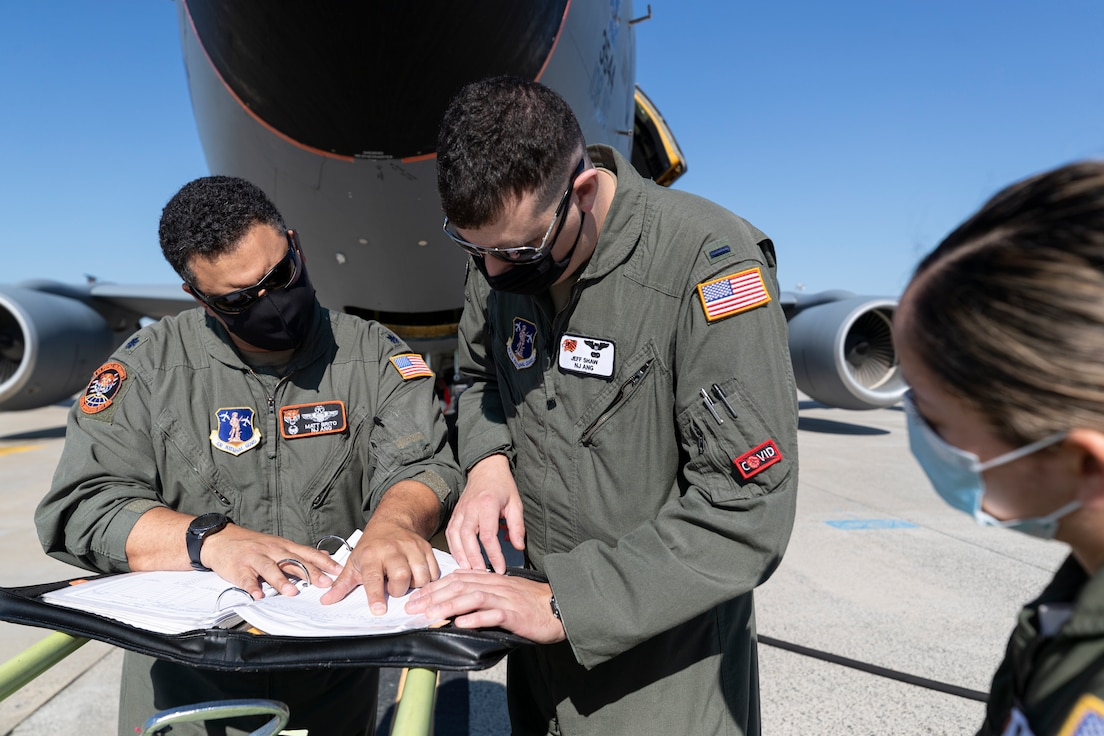 """U.S. Air Force Lt. Col. Matthew Brito, left, 1st Lt. Jeff Shaw, and Staff Sgt. Kimberly Moncayo, all with the New Jersey Air National Guard's 141st Air Refueling Squadron """"Tigers"""", go over pre-flight checklists on Joint Base McGuire-Dix-Lakehurst, N.J., May 27, 2021."""