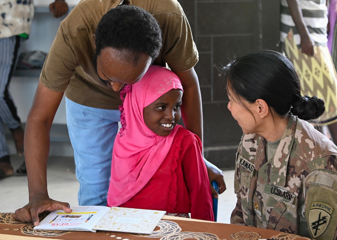 U.S. Army Reserve Maj. Sachiyo Kawaguchi, a dentist assigned to Civil Affairs East Africa Southern European Task Force Africa functional specialty team, in support of Combined Joint Task Force-Horn of Africa, reads with a child at the new Ali Adde school library, in Ali Adde, Djibouti, May 27, 2021. The new library was a U.S.-funded construction project which created local jobs and was built by a Djiboutian construction company employing Djiboutian laborers.