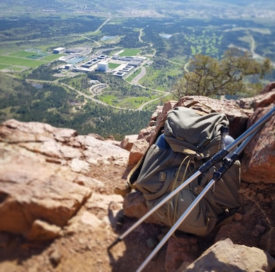 A backpack and trekking poles rest against a rock on Eagle's Peak, overlooking the Air Force Academy in Colorado Springs, Colo.