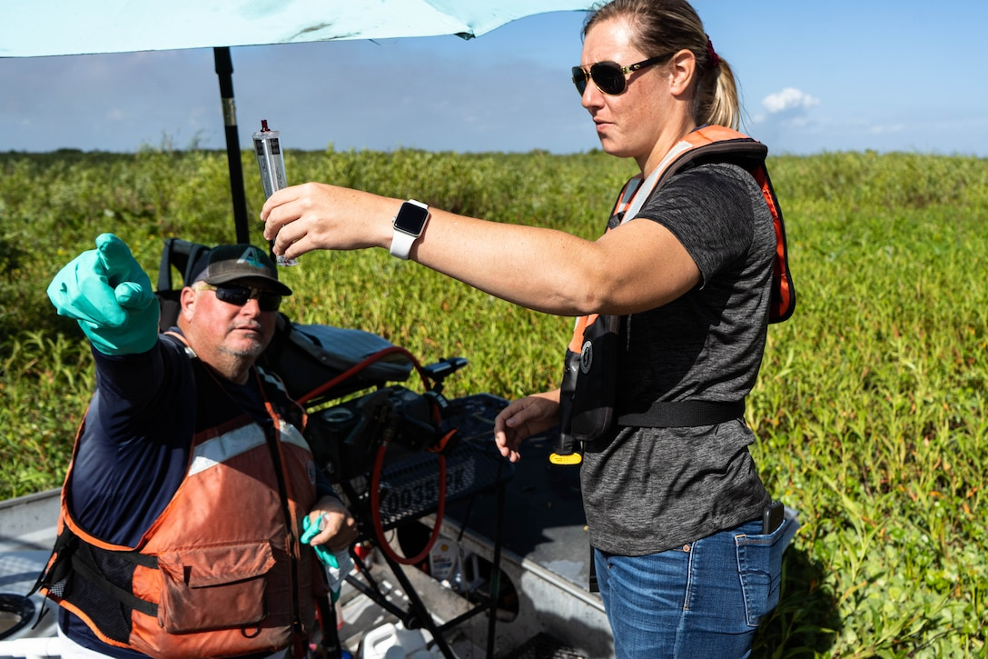 Applied Aquatics, licensed applicator, Jeff Smith and U.S. Army Corps of Engineers, biologist Jessica Fair discuss how wind plays an important role when managing invasive aquatic plants with chemical sprays. Fair, holds up a Portable Series Wind Meter which is used to indicate wind speed. Licensed applicators use this device along with guidance from the Environmental Protection Agency to determine whether or not to spray invasive aquatic plants.
