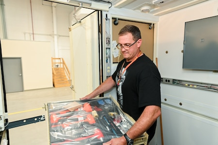 Photo of Alan Baker installing furniture and equipment into the ARSS V2.