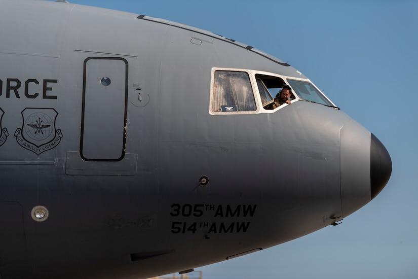 Photo of an Airman looking of a KC-10 Extender window.