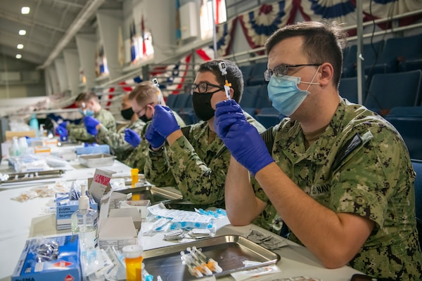 Medical personnel from the Captain James A. Lovell Federal Health Care Center (FHCC) and the surrounding Great Lakes area prepare vaccinations for use inside Pacific Drill Hall at Recruit Training Command (RTC).