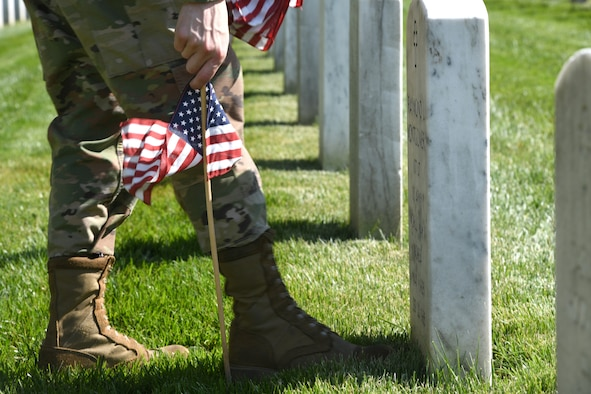 Close up of hand pushing flag into ground.