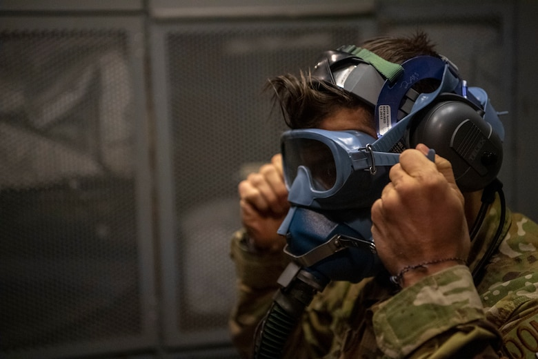 Photo of an Airman checking an oxygen mask prior to take off.