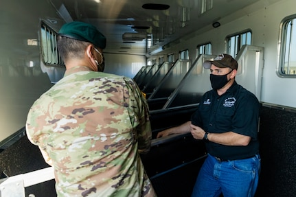 U.S. Army Sgt. 1st Class Timothy French, right, assigned to the U.S. Army North Caisson Platoon, describes the advantages of the stalls located in the caisson platoon's new trailer to Lt. Col. Richard Teta, left, U.S. Army North battalion commander on Joint Base San Antonio - Fort Sam Houston, April 8, 2021.