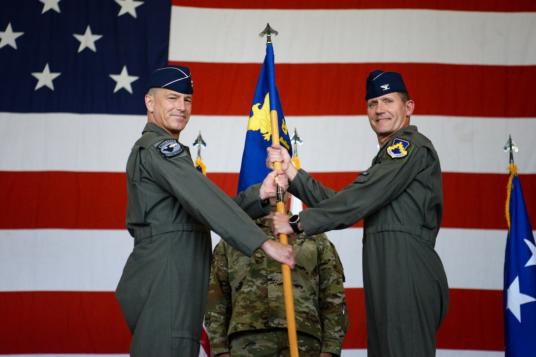 Two commanders hold a guidon during a ceremony.
