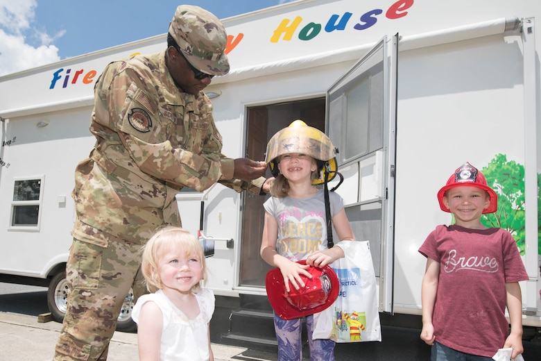 Staff Sgt. Marcus Scriven, 436th Civil Engineer Squadron crew chief, puts a firefighter helmet on Emma Peterson during the 2021 Hurricane Block Party at Dover Air Force Base, Delaware, May 27, 2021. The block party, sponsored by the 436th CES Emergency Management flight, offered attendees useful information pertaining to severe storms and hurricanes. (U.S. Air Force photo by Mauricio Campino)