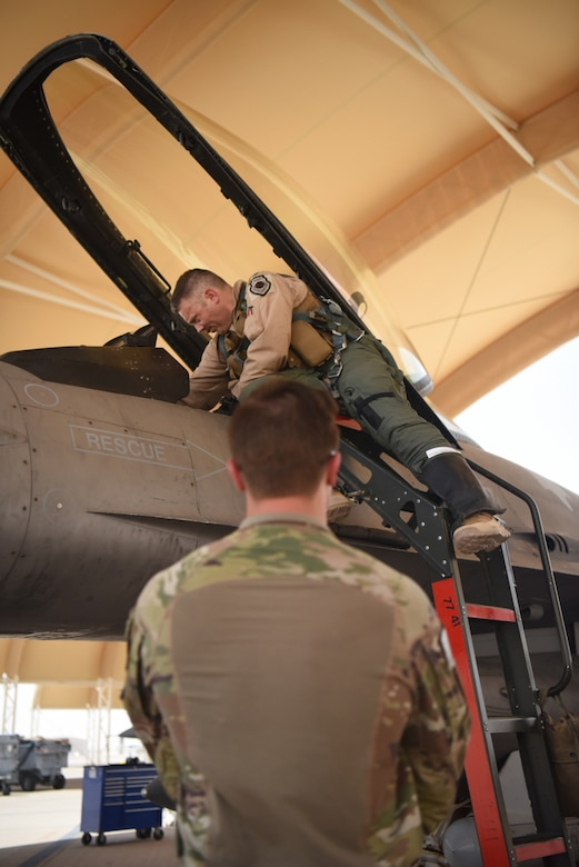 """Col. Kristoffer Smith, 378th Expeditionary Operations Group commander, prepares for a flight aboard an F-16 Fighting Falcon fighter jet for takeoff at Prince Sultan Air Base, Kingdom of Saudi Arabia, May 16, 2021. The """"Swamp Fox"""" Airmen from the South Carolina Air National Guard deployed to PSAB to project combat power and help bolster defensive capabilities against potential threats in the region. (U.S. Air National Guard photo by Senior Master Sgt. Carl Clegg)"""