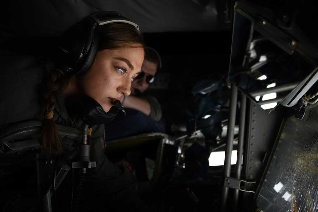 An airman looks out the window of a military aircraft.