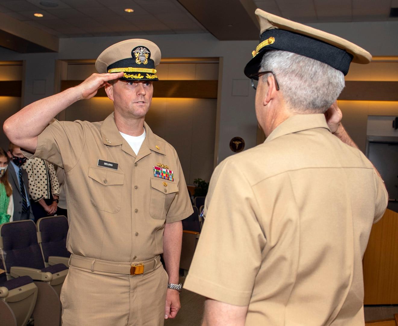 Gerald Delong salutes Capt. Adam Armstrong, as he assumes command.