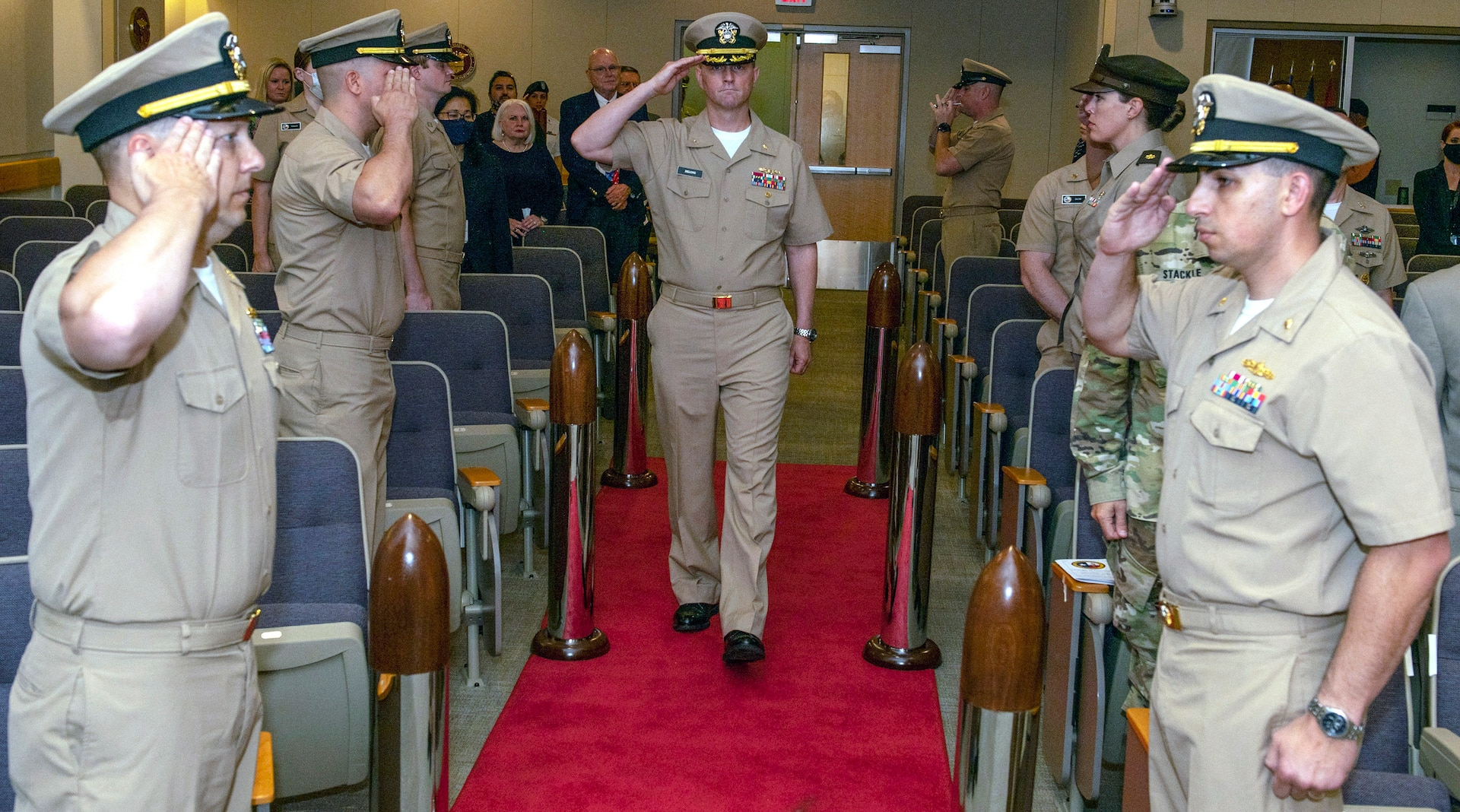 Navy Capt. Gerald DeLong, incoming commander for Naval Medical Research Unit-San Antonio, is saluted by the sideboys