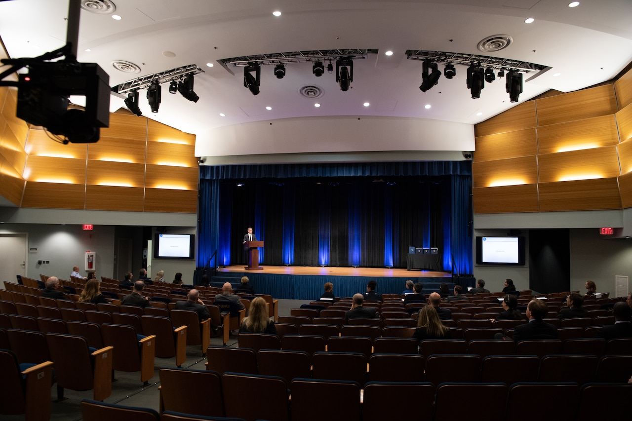 A man on a stage speaks to socially distanced people seated in an auditorium.