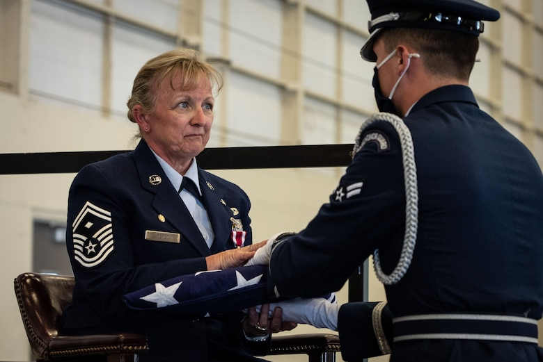 Honor guardsman hands folded American flag to crying female Airman.