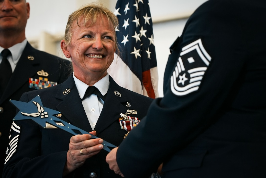 Woman in dress blues receives wand.