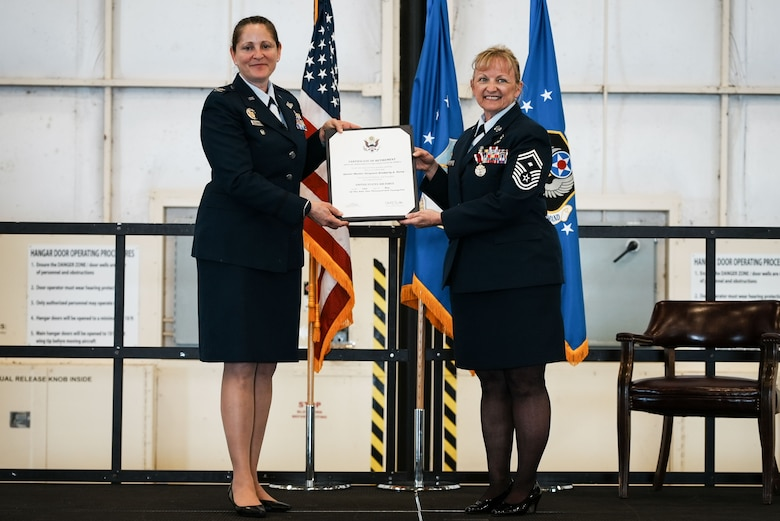 Two women in dress blues hold a certificate on a stage.