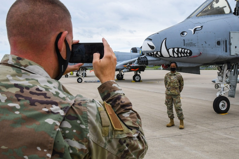 A photo of an airmen taking a picture of another airman in front of a jet