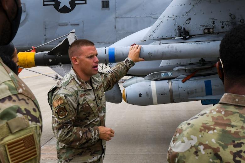 A photo of an airman talking next to a jet
