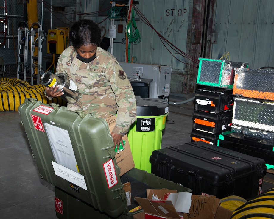 female Airman packing packaged materials inside a medium sized green storage case