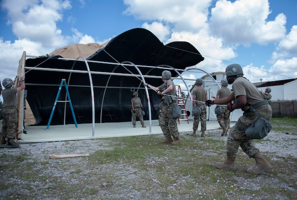 Airmen pull a rope to put up a tent.