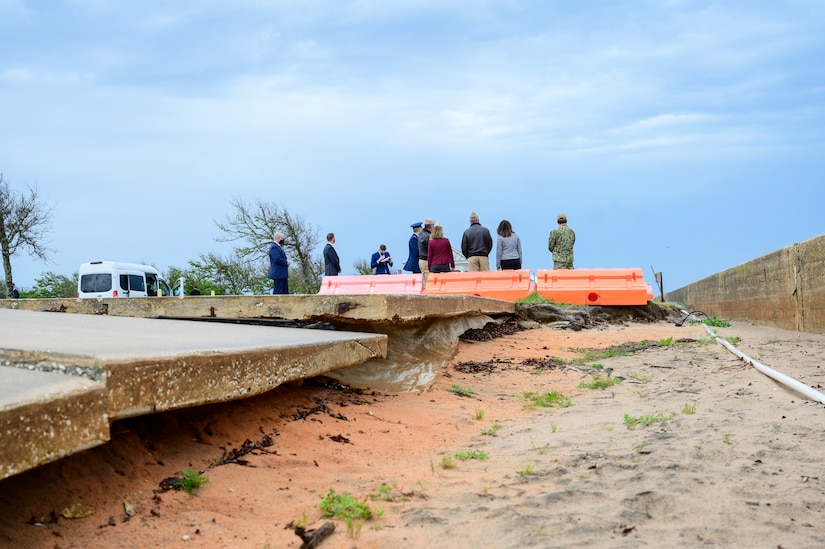 A photo shows the backs of eight people who are looking at something in the distance as another person appears to take notes. In the foreground, barricades block off an area where sand has eroded beneath a concrete slab.