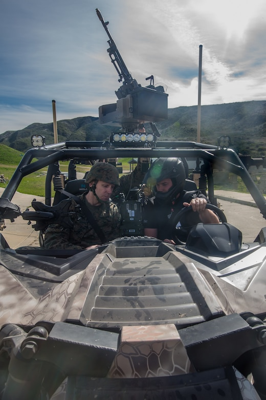 Two Marines sit in a tactical vehicle.