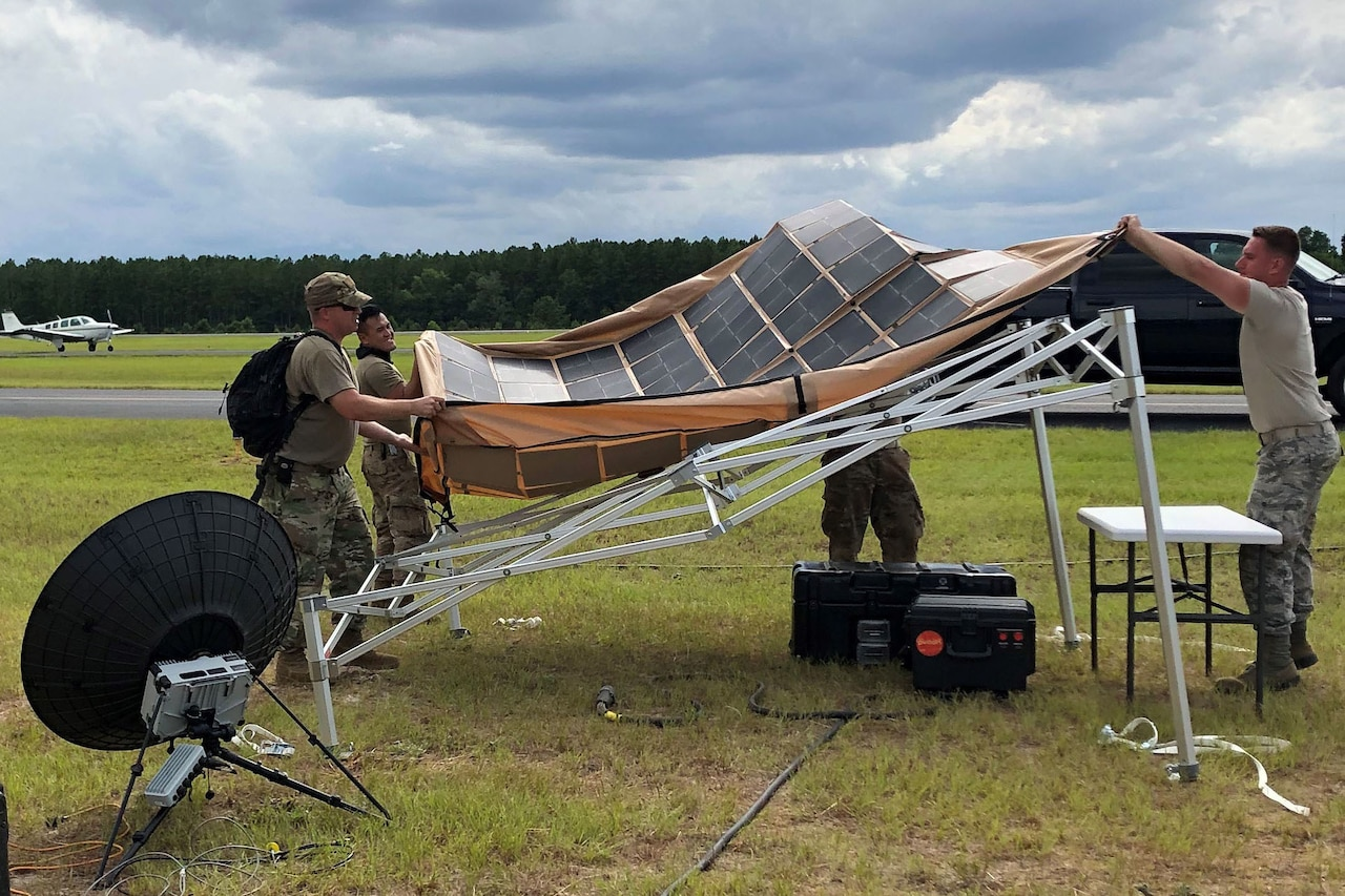 Airmen spread out a tarp covered with solar panels.