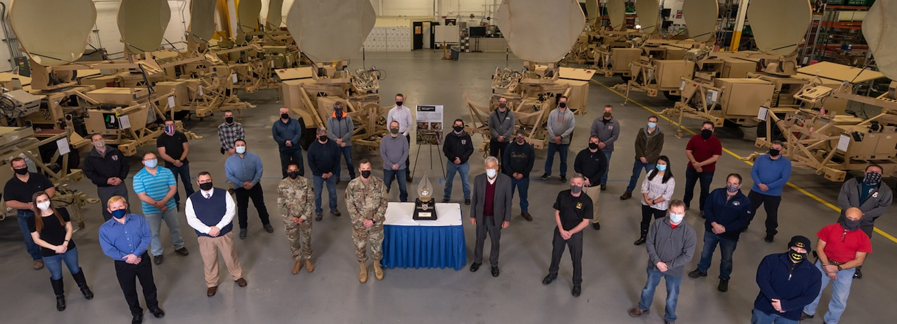 Photo of Employees and Command Group personnel standing around the award in the STT shop