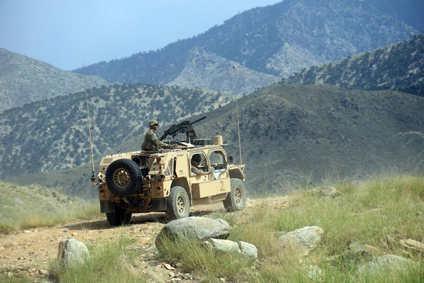 A combat vehicle along a gravel road with mountains in the background.  A soldier sits atop the vehicle near a gun that is mounted on the roof.