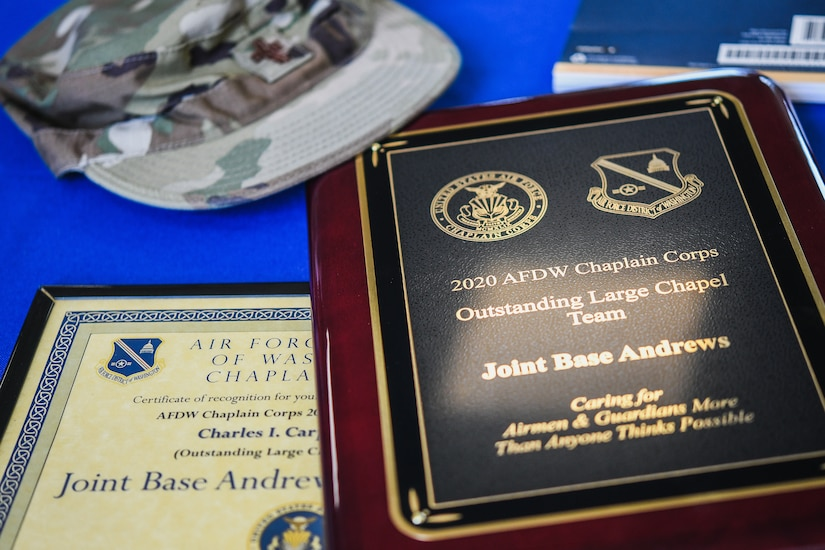 A Charles R. Meier Award and an Outstanding Large Chapel Team Award sit on the table during the 2020 Annual Awards Presentation at Chapel 1, Joint Base Andrews, Md., May 18, 2021. (U.S. Air Force photo by Airman 1st Class Bridgitte Taylor)