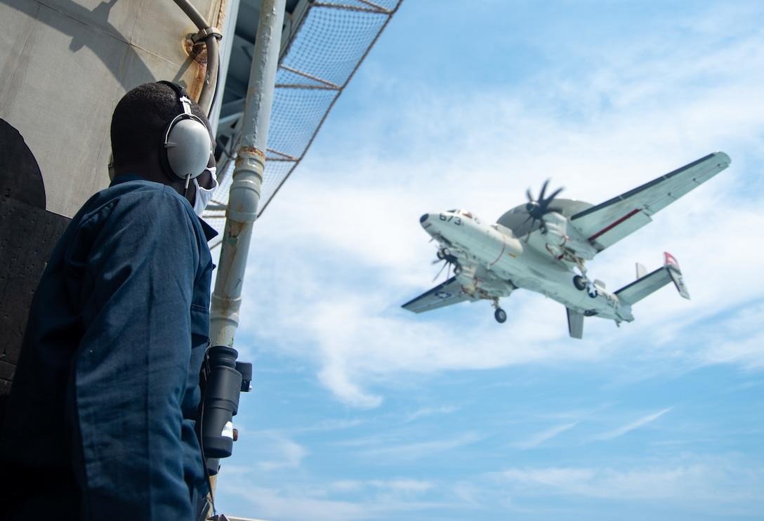 A sailor stands on a ship as an aircraft flies over.