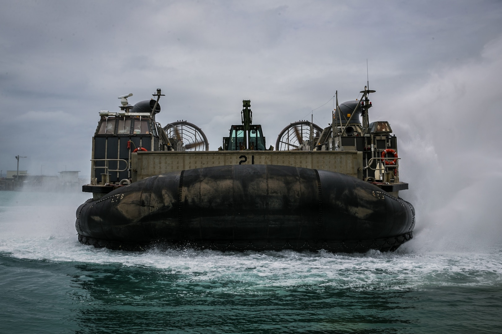 A U.S. Naval Landing Craft Air Cushion (LCAC) maneuvers into the ocean from Port Operations, Naval Base White Beach, Okinawa, Japan, June 1, 2021. Marines from 3d Marine Logistics Group (MLG) and Sailors from Naval Beach Unit (NBU) 7 integrated to load and transport personnel and equipment in support of exercise Poseidon's Watchtower. NBU-7 is an operational, forward deployed unit that directly contributes to the core capabilities of U.S. Maritime Sea Power by facilitating the movement of troops, equipment, vehicles and supplies from amphibious shipping across the beach. 3d MLG, based out of Okinawa, Japan, is a forward deployed combat unit that serves as III MEF's comprehensive logistics and combat service support backbone for operations throughout the Indo-Pacific area of respons