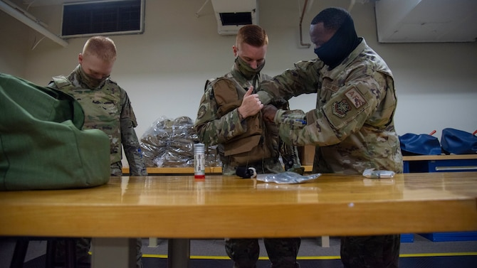 U.S. Air Force Tech. Sgt. Chris Battle, 6th Operations Support Squadron (OSS) Aircrew Flight Equipment (AFE) NCO in charge of aircraft operations (right) inspects a vest worn by Airman 1st Class Daunte Morrison, 6th OSS AFE journeyman (middle) while Airman Nikolai Wroblewski, 6th OSS AFE apprentice (left) waits for his vest inspection at MacDill Air Force Base, Florida, April 14, 2021. 6th OSS AFE members must be fully trained on lifesaving equipment and survival components as well as keep air crews trained and proficient on the use of such equipment.