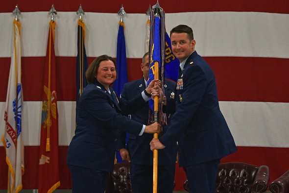 U.S. Air Force Col. Angelina Maguinness, 17th Training Group commander, passes the guidon to Maj. Samuel Logan, incoming 312th Training Squadron commander, during the change of command ceremony at the Louis F. Garland Department of Defense Fire Academy High Bay on Goodfellow Air Force Base, Texas, June 1, 2021. Logan was the flight commander for the 1st Special Operations Civil Engineer Squadron at Hurlburt Field, Florida. (U.S. Air Force photo by Senior Airman Ashley Thrash)