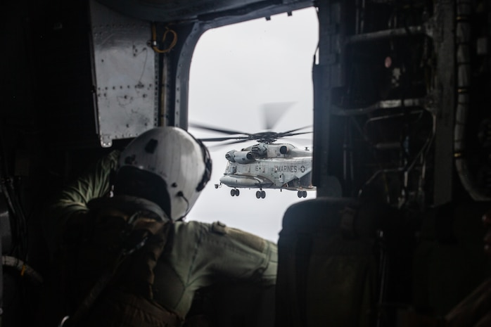 A U.S. Marine with Medium Marine Tilt Rotor Squadron 265 (VMM-265) Reinforced, 31st Marine Expeditionary Unit (MEU), views a CH-53E Super Stallion flying during a helicopter raid training exercise over Okinawa, Japan, May 25, 2021.