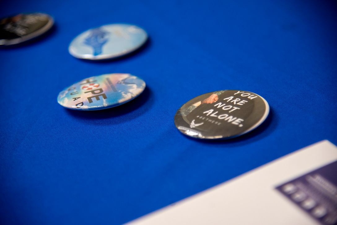 Four buttons with suicide prevention messaging sit on a presentation table during an Applied Suicide Intervention Skills Training (ASIST) course, led by Air Force Wounded Warrior Program (AFW2) leaders, at MacDill Air Force Base, Florida, May 12, 2021. Suicide prevention and Airmen's resiliency remain a top priority for the U.S. Air Force and Team MacDill.