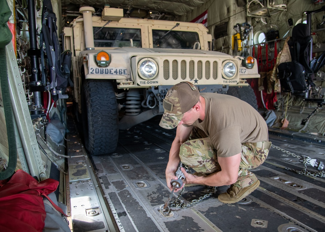 Tech. Sgt. Christopher Townsley, loadmaster for the 815th Airlift Squadron at Keesler Air Force Base, Miss., tightens chains to secure a High Mobility Multipurpose Wheeled Vehicle onto a C-130J Super Hercules during Voyager Shield, an exercise hosted by the 621st Air Mobility Advisory Group at the Joint Readiness Training Center and Fort Polk, La., May, 25, 2021. The joint forces exercise, Voyager Shield, consisted of the 621st AMAG, the Army JRTC and Fort Polk and the Air Force Reserve from the 403rd Wing, took place from May 25-27 and for the 815th AS required tactical training consisted of loading and offloading of rolling cargo and personnel air drops. (U.S. Air Force by Staff Sgt. Kristen Pittman)