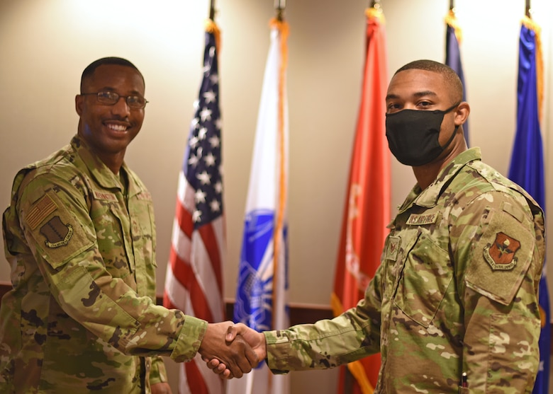 U.S. Air Force Chief Master Sgt. Marcus Washington, 17th Medical Group superintendent, coins Staff Sgt. Nigel Jaggard, 17th Logistics Readiness Squadron logistics planner, at the 17th Training Wing Spotlight in the Norma Brown building on Goodfellow Air Force Base, Texas, May 20, 2021. Jaggard was chosen as the 17th TRW Spotlight for his hard work in the mission to train, develop, and inspire the future force. (U.S. Air Force photo by Senior Airman Abbey Rieves)