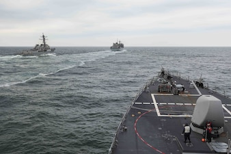 USS Ross (DDG 71), right, USNS Supply (T-AOE 6), center, and USS Roosevelt (DDG 80) conduct a replenishment-at-sea.