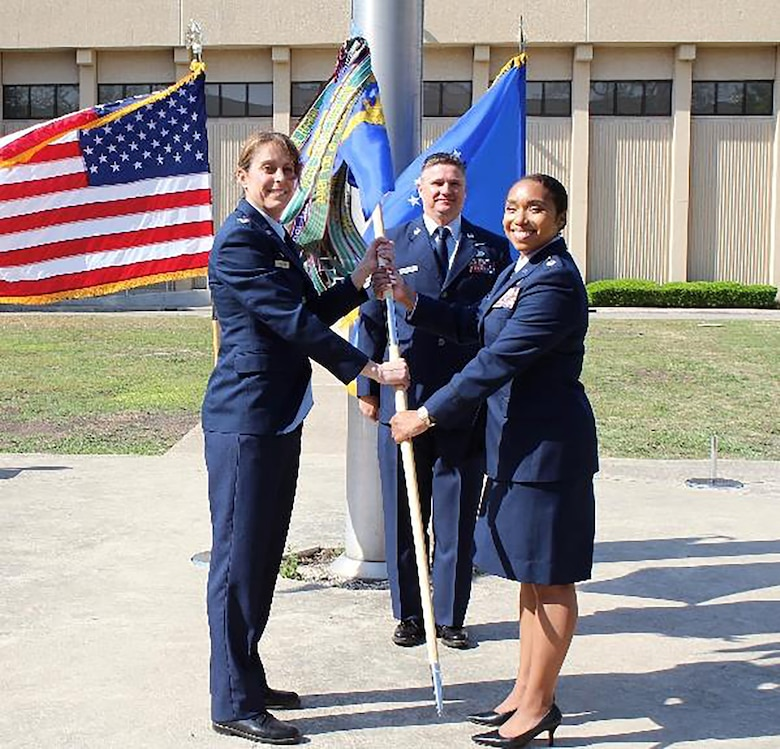 """Col. Jennifer Mulder, commander of the 655th Intelligence, Surveillance and Reconnaissance Group, passes the guidon to incoming 23rd Intelligence Squadron commander, Lt. Col. Stephanie """"Chappy"""" Hahn as Senior Master Sgt. David Stanford, 23 IS operations superintendent, looks on."""