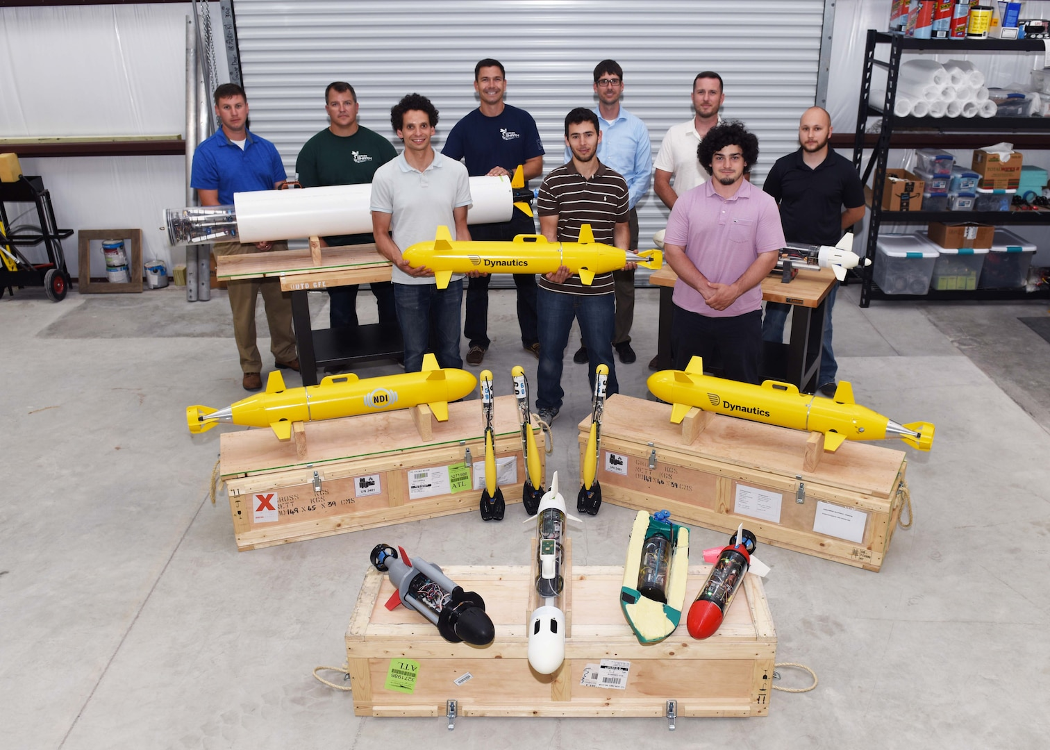 """Lead scientists and engineers from Naval Sea Systems Command Warfare Center Divisions pose for a photo as a representation of a collaborative and innovative effort in development of modular, inexpensive unmanned systems collectively known as the """"microSwarm Family of Systems,"""" or """"µFOS."""""""