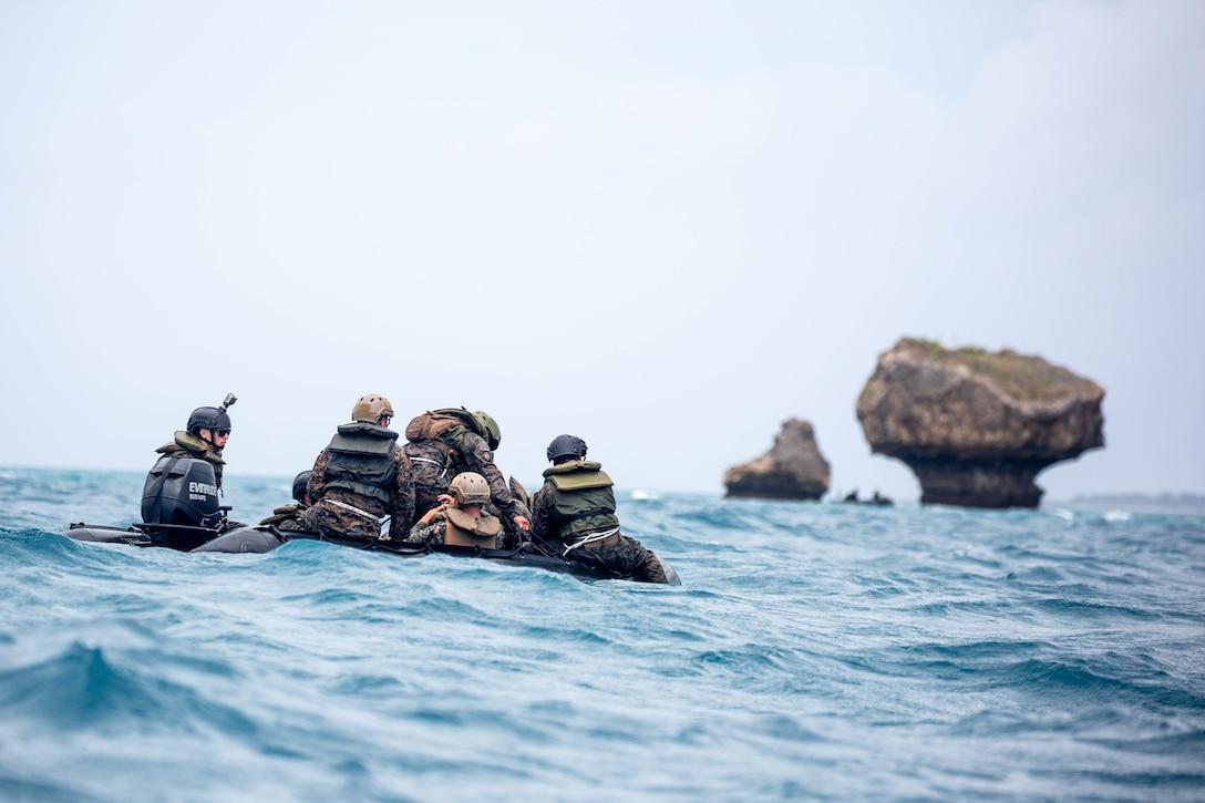 Marines ride in a small boat near rocks.