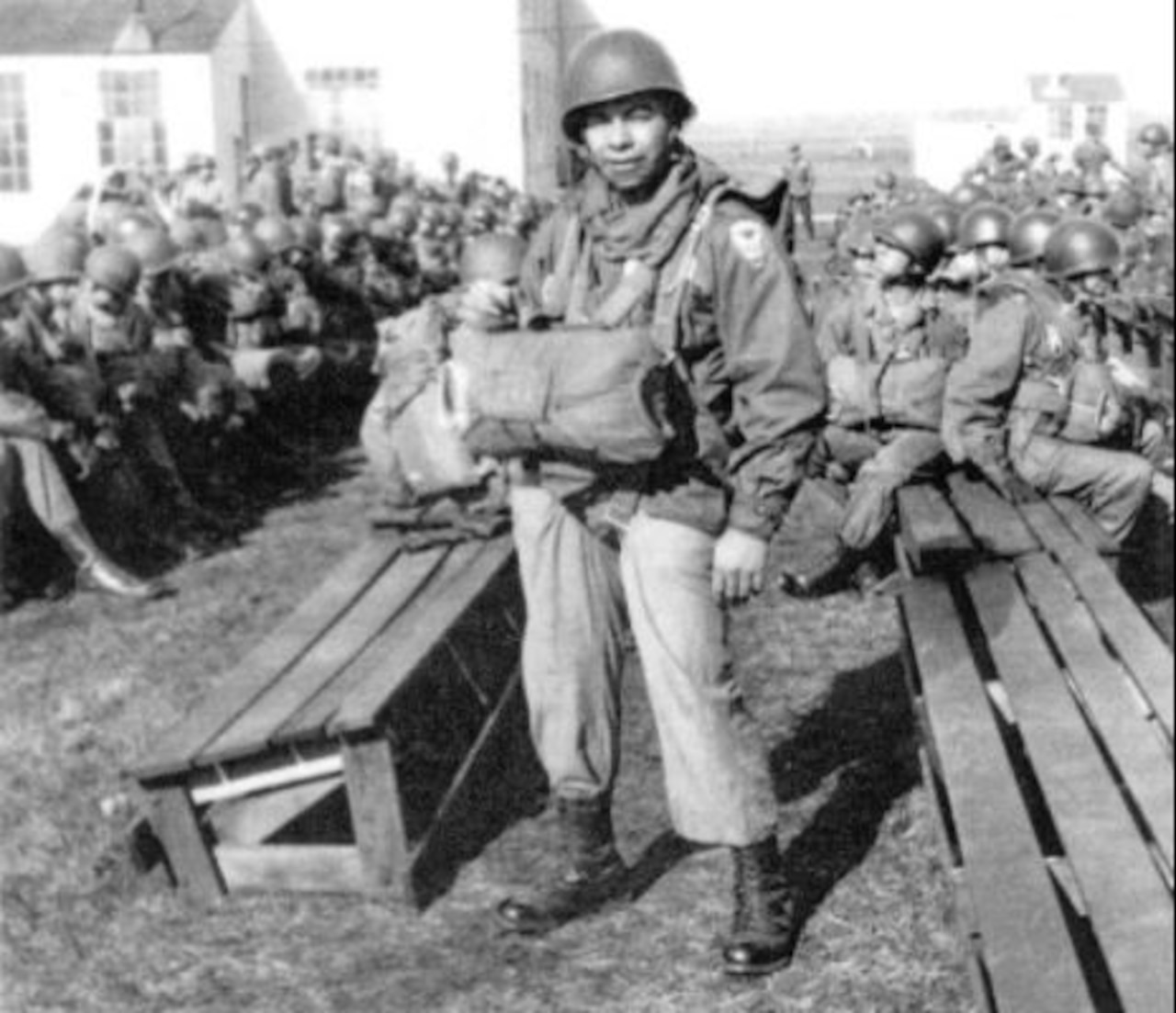A man wearing a front-loaded parachute stands in the foreground with other men seated on benches behind him.