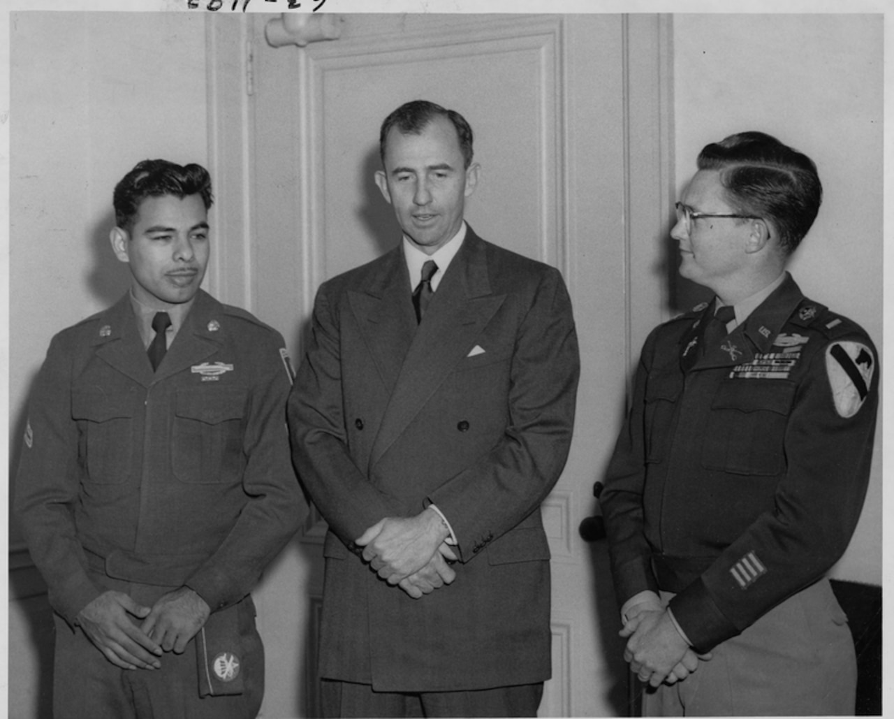 Three men stand side by side with their hands folded beneath their waists.