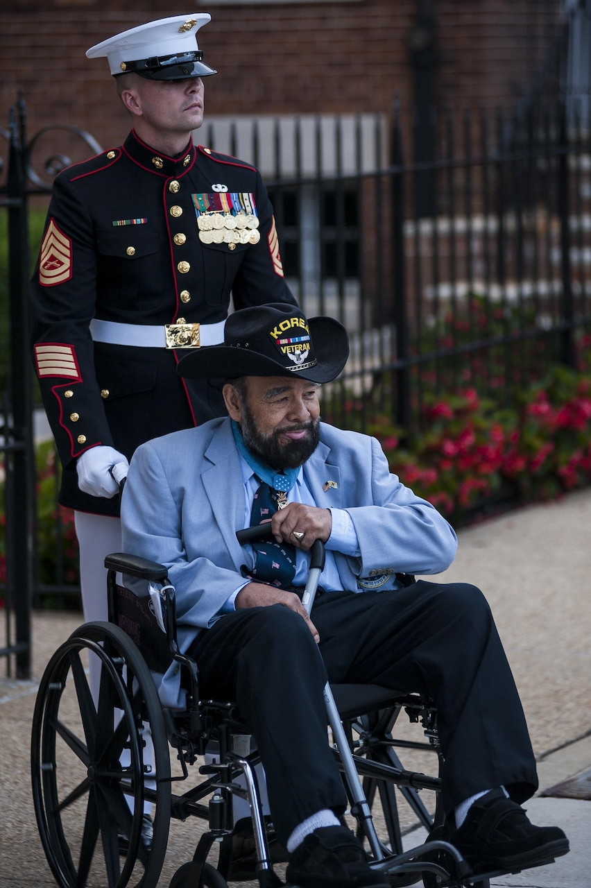A Marine in dress uniform pushes the wheelchair of an older man in a cowboy hat.