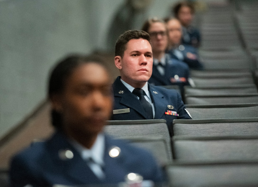 Staff Sgt. Nicholas Harris-Duke, National Air and Space Intelligence Center, listens with other graduates to the commencement address during the Community College of the Air Force spring graduation ceremony May 26, 2021, in the theater at Wright-Patterson Air Force Base, Ohio. Harris-Duke earned an associate's degree in intelligence studies and technology. (U.S. Air Force photo by R.J. Oriez)